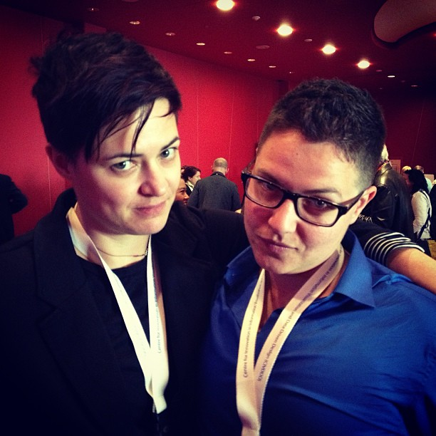 Two light-skinned queer women with short haircuts raising their eyebrows while facing the camera. The one on the left is wearing a black shirt and has her arm around the one on the right, who is wearing a blue shirt and glasses.