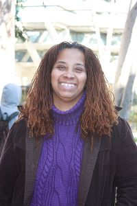 An African American woman, smiling, with shoulder-length hair, in a purple knitted turtleneck with a black jacket over it.