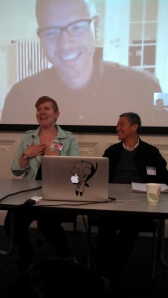 Two people sit in front of a screen on which is projected the face of another person. They are all laughing. A laptop is in the foreground.