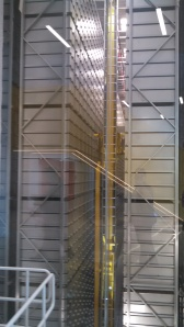 A gigantic warehouse of drawers, with a yellow robotic frame, resembling a ladder, towering in the center.