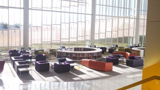 Against a paned glass wall, colorful lounge chairs cluster around a round bookcase.