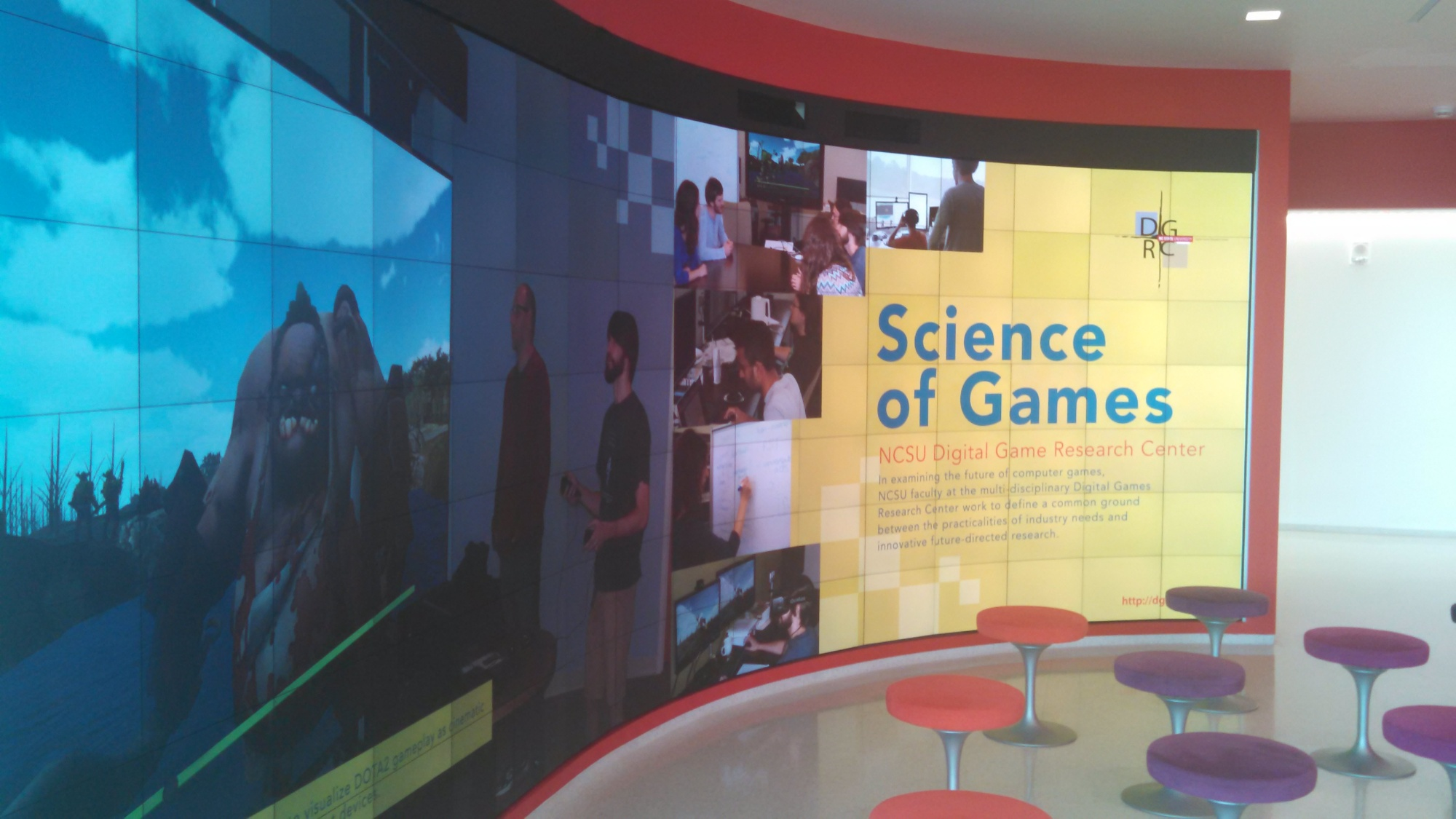 "A wall-sized screen, curved inward. It depicts scenes from various video games, and on the right reads ""Science of Games: NCSU Video Game Research Center."" Illegibly small text underneath."