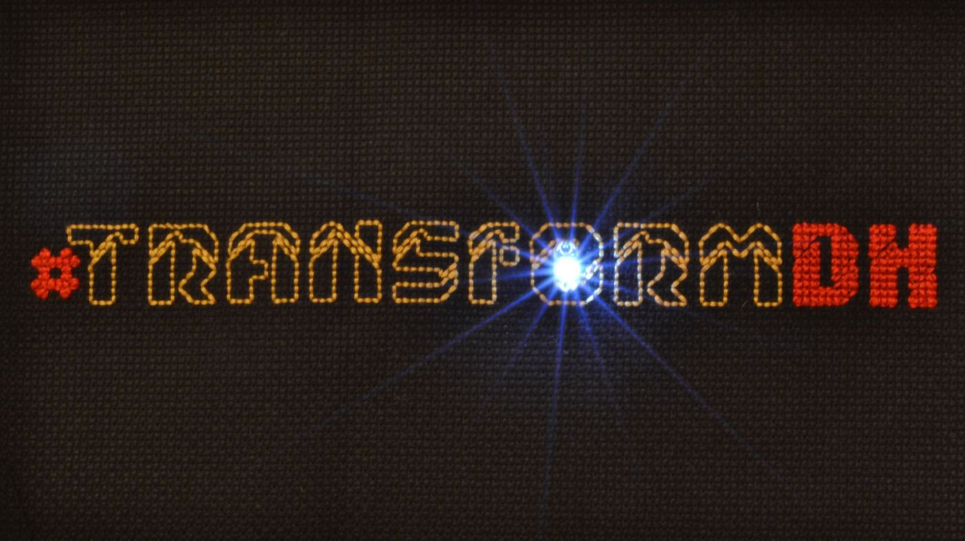 Stitched text that reads #transformDH, with an LED shining through the O. Logo/stitching: Melissa Rogers Photo: Reed Bonnet