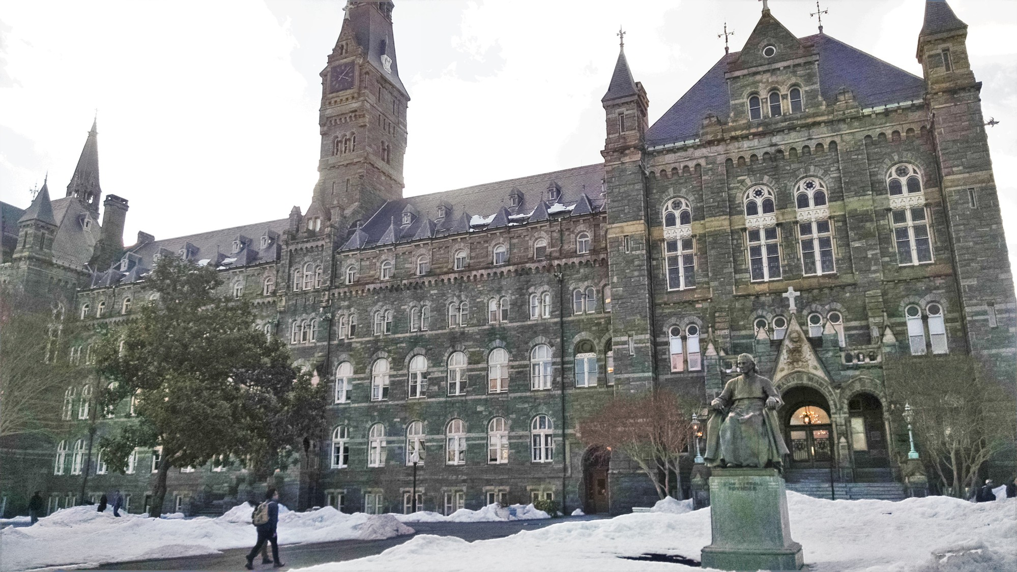 A picture of Healy Hall at Georgetown University, a large, neo-Medieval structure made of dark bricks, with arched windows and a clock tower. In front of the building is a statue of Bishop John Carroll, founder of the university.