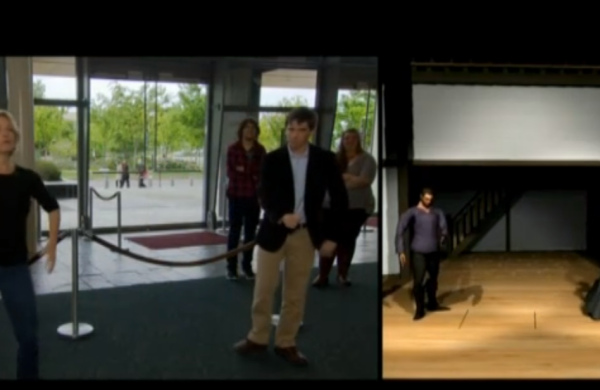A split screen. On the left side, a white woman and white man performing in front of velvet ropes. On the right, a virtual scene with a male and female avatar mimicking their actions.