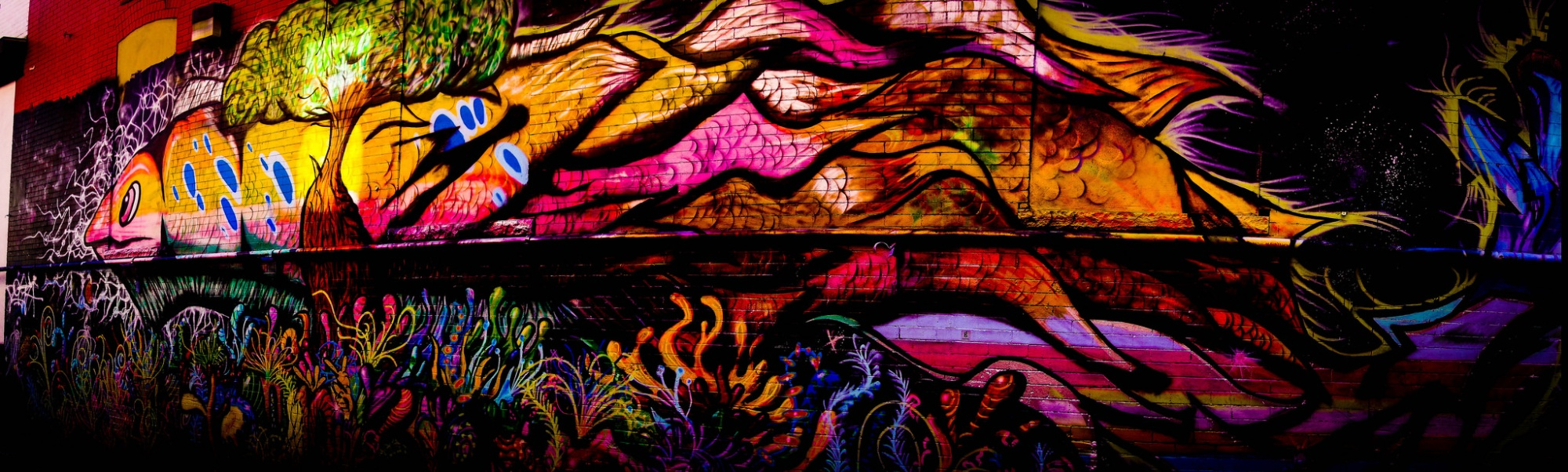 A nighttime mural scene: in neon colors, a tree in front of a giant fish. The bottom half is a neon waterscape with coal. The fish is both in and out of the water.