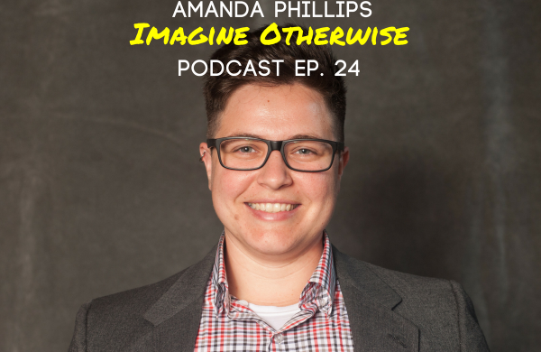 "A headshot of a light-skinned butch woman with short hair and glasses wearing a read and black checkered shirt and gray blazer. At the top, ""Amanda Phillips Imagine Otherwise Podcast Ep. 24"