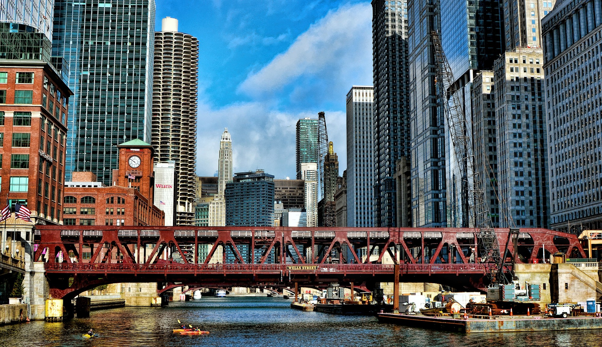 Image of the Chicago skyline, looking down the river with a red bridge over it, skyscrapers on either side. It is a sunny day and kayakers are paddling in the water.