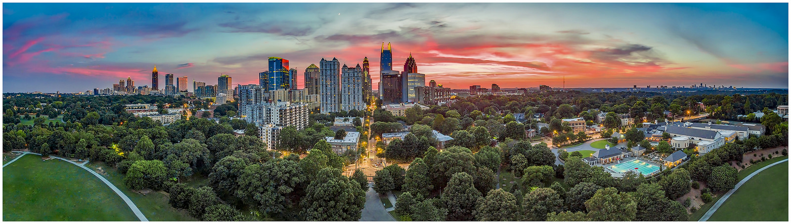 "A panoramic view of the skyline of Atlanta, with trees in the foreground and the sky turning pink from the sunset in the background. ""Fire in the Sky,"" by Richard Cawood. Licensed under CC BY-NC-ND 4.0."