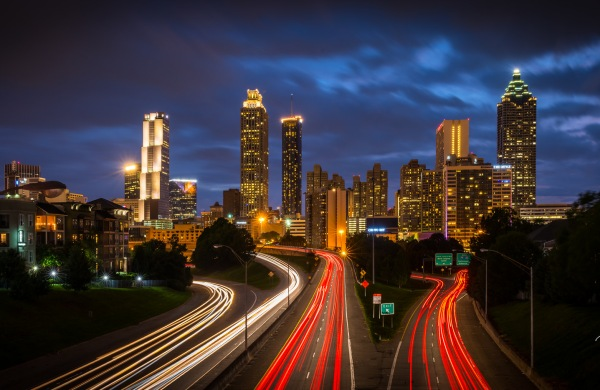 "A nighttime time lapse of the Atlanta skyline, with clouds overhead and red and white streaks from car lights on the highways. In the corner, a watermark that reads Rudy Wilms Photography. ""Atlanta Skyline from Jackson Street Bridge,"" by Rudy Wilms. Licensed under CC BY-NC-ND 2.0."